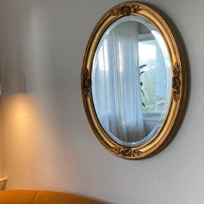 """Antikt og ovalt facetskåret guldspejl med krummelure. Måler ca 61 x 82 cm. Jeg har haft stor gavn af det i nogle år, men nu er det tid til at finde en ny ejer.  Det står som """"slidt"""", men det er det som sådan ikke! Det er gammelt men det er en del af charmen.  Spejlet har 2 snore bagpå, så man både kan hænge det vertikalt og horisontalt :)  Sender ikke, men kan hentes på min adresse i København S (Amager) Der er mulighed for at få det bragt, hvis du ikke bor for lang væk, for en 50'er ekstra."""