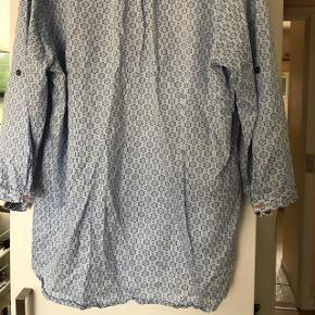 Skjorte med knap midt på ærmet, så det også kan være i 3/4 længde. Skjorten er meget mere lyseblå/hvid end billeder viser