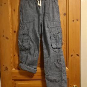 Varetype: Bukser med opsmøg Farve: Blå  Smarte bukser i 100% bomuld med mulighed for at folde buksebenene op og knappe dem fast.   Kan sendes med DAO for 35 kr😊