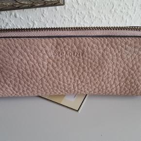 Maya 354 Pencil case i soft pink er et penalhus i gennemfarvet skind med struktur. Det er foret og lukkes med lynlås. Brug det til at opbevare skriveredskaber, briller eller makeuppensler.  23 x 6 x 5 cm  Makeup pung - penalhus mm  Ubrugt, nypris 560