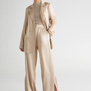 Nyt, med tags! Champagne satin suit fra Gina Tricot. Bukserne er str 34 og blazeren er str 38, men begge fitter lidt oversized. Prisen er for sættet!