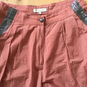Fine bukser fra Wackerhaus i tyndt, let stof med smal strib i rød og lyserød. Detaljer i mørk sølv. Lidt baggy model. Bred elastik forneden.  Brugt meget lidt - måske 3 gange. Jeg synes, at de to første billeder viser farven bedst.