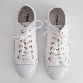"""Hvide Chuck Taylor sko med """"guld"""" detaljer. Fremstillet i syntetisk læder. Har, trods brugsspor på snude og sål, kun været gået i 2-3 gange, og sælges kun fordi jeg desværre ikke kan passe dem. Købt sidste forår for ca. 500 kr. Pris: 200 kr. plus porto"""