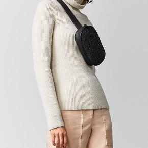 Bottega Veneta intrecciato bælte taske i sort. Den er i Bottega Veneta klassisk intrecciato napp læder. Den er oval formet og kan bruges både som crossbody eller mave-taske. Der er en lille lomme på indersiden med en knap på og ellers er det et stort rum. Mærke, certifikat, dustbag og pose fra butikken medfølger.  Jeg har ikke besluttet mig for om den skal sælges endnu.  Respekter venligst at jeg ikke bytter og køber betaler porto samt gebyret ved tshandel.