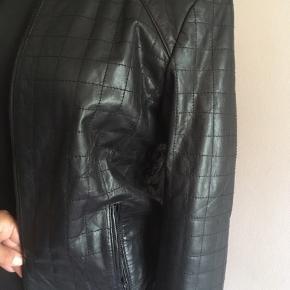Flot sort læderjakke m. kvadratisk struktursyning, lynlås, lynlåslommer i siden og elastik i ærmekanter samt talje.  Str. 40, der bedst passer en M eller L med medium barm. En smuk og lidt anderledes læderjakke med fine detaljer, der samtidigt gør den stilet. Ny og ubrugt.  Pris ved afhentning i Nordsjælland ellers + porto.