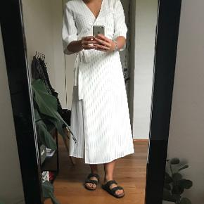 Hvid lang slå-om-kjole med striber. Kun prøvet på, så fremstår derfor som helt ny.
