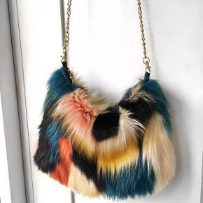 Imiteret pels i flere farver, med guldkæde  Måler 26x20 cm  Prisen er inkl. levering - afhentes der i Valby trækkes 38 kr fra 😊