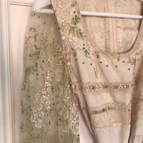 Gudesmuk prinsesse vintage kjole med fine detaljer som broderede blade og blomster samt små similisten på ærmer og skuldre, pyntebånd i grøn velour, kniplinger på det gennemsigtige stykke af ærmerne. Guldknapper ved ærmerne. Kjolen kommer med et separat yderskørt med brede bindebånd og samme udsmykning som overdelen. Kunne evt. fungere som en anderledes brudekjole.