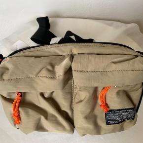 Khaki / sandfarvet / mørk beige farvet unisex bæltetaske / bumbag / cross body - kan styles på flere måder - fra UO Orange detaljer - de orange bælte regulerings stropper kan evt klippes af:-) Praktisk materiale poly / nylon Lille lynlås rum i det store rum og to lommer foran med Zip. Bredde ca 25 cm Højde ca 17-18 cm Dybde 8 cm uden front lommer og ca 10 cm med lommer. Lang regulerbar rem ca 95 cm #Secondchancesummer Sælges for 170 plus TS gebyr & Porto Hvis afhent 170