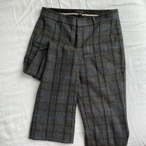 Banans Republic Bukser i modellen Logan  I grå uld med tynde blå striber  Str. 0 Petite (svarende til en XS/34) Indvendig benlængde: ca. 73 cm  De er brugt lidt men fejler intet