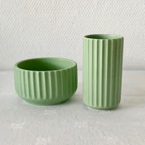 Matgrøn Lyngby vase og skål.Lyngby vasen på 12 cm er den næstmindste porcelænsvase i Lyngbys sortiment.  Smuk og stilfuld til små buketter eller enkeltstående blomster.  Lyngby vasen på 12 cm er også rigtig fin til f.eks. tandbørster eller børster og kamme, der står frit på badeværelset. Eller til dit skrivebord til tuscher, blyanter og pensler. Den pynter ganske enkelt uanset hvor du placerer den – og om du sætter noget i den eller ej. Står den alene bliver den en fritstående skulptur i sig selv. Stiller du den sammen med andre størrelser Lyngby vaser, bliver den et harmonisk samlingspunkt. Den udstråler ro og klassisk skønhed, uanset hvor og med hvad du placerer den. Lyngby skålen på 11 cm er en glimrende størrelse til alt fra snacks, morgenmadsservice, dessert-skåle, skåle til tilbehør eller blot som en enkeltstående smuk skål, der skaber ro og harmoni hvor den end stilles. Tåler ovn op til 180° C. og opvaskemaskine. Mål på skål: 11 cm D x  6,5 cm H Mål på vase: 12 cm H x 6,5 cm B Pris for vase: 125 kr Pris for skål: 150 kr Samlet tilbud: 225 kr 2. sortering