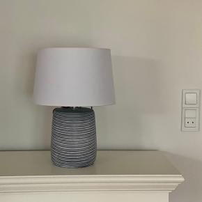 Grå stribet keramik lampe med hvid lampeskærm fra Jotex. Højde 42 cm med lampeskærm. Lampeskærm; 29 cm i diameter. Standen er stort set som ny. Bytter ikke :)