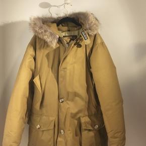 Sælger min kærestes Woolrich Artic Parka. God og varm vinterjakke, mangler en knap (tredje nedereste) og er et mindre hull i jakkelommen, dog ikke synlig.   Sælges til højst bydende!