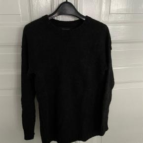 Mørke grå strik sweater med udvendige syninger. Str. S. Strikken er godt brugt og har div brugsspor og sælges derfor til en god pris