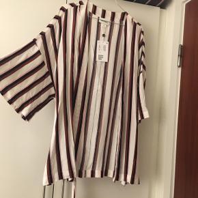 Flot kimono fra Monki med bindebånd i hvid med flotte farvede striber.  Str. M, men tænker den passer både M, L og XL grundet de vide ærmer.  Aldrig brugt og stadig med prismærke.   Nypris: 200kr. Sælges for: Bud tættest på 200kr.
