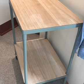 Fint lille barbord fra Søstrene Grene.  Lys træ med grønt metal stel. Sælges pga pladsmangel. Målene er 65 i højden, 50 i bredden og 35 i dybden.
