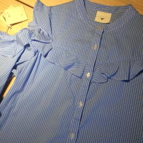 Smuk skjorte med feminine detaljer. Åbne skuldre.  Billede med den på i kommentar (bukserne er også tilsalg).  Brugt en håndfuld gange.
