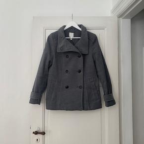"""Dobbeltradet figursyet frakke, med for. Størrelse 42. Brugt i 3-4 måneder, men ellers i fin stand. Se sidste billede, for bedre forståelse for frakkens farve.  Materiale: 2% Elastan, 12% Viskose & 86% Polyester. Foret i jakken er 100% Polyester.  Prisen er fast☀️ Benyt gerne """"køb nu"""" funktionen⬆️☀️"""