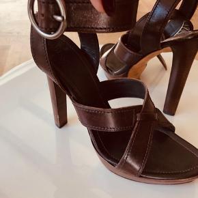 Yves Saint Laurent sandaler stiletter i brunt skind med flotte syninger. Platform sål gør dem super behagelige. Krydses op over anklen med fedt spænde. Købt i Paris