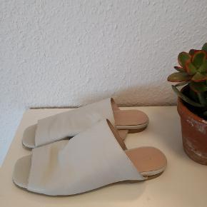 Lækre slippers/sandaler fra Bianco i hvidt blødt læder. Har en lille hæl. Kun prøvet på indendøre. Købt for ca. én uge siden, men må desværre erkende, jeg ikke får dem brugt.   ▪️Sender gerne/køber betaler porto  ▪️Porto fra 38 kr. med dao  ▪️Fra dyrefrit og røgfri hjem  ▪️Returnerer ikke  ▪️Køber betaler ts gebyr (ca. 2 kr.)