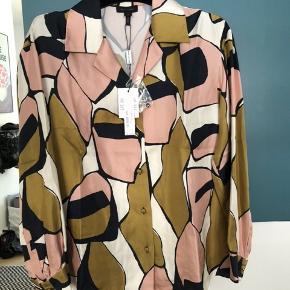 """Jeg overvejer at sælge denne smukke silkeskjorte fra Marc Jacobs, skjorten er helt ny med prismærke og er kun prøvet på, sælges, da jeg har så meget tøj. Falder smukt pga. den """"tunge"""" silke. Kommer fra et ikke ryger hjem og ikke dyre hjem.  Jeg bytter ikke, respekter venligst dette. Samtidig betaler køber gebyr ved tshandel (sælger og køber)   ❤︎ 100% silke  ❤︎ Mål: Skulder: 44 cm"""