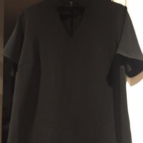 Smuk sort bluse med korte ærmer i lækker viskose. Aldrig brugt.
