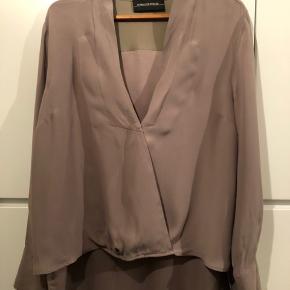 Silkeskjorte fra by Malene Birger. Super lækker kvalitet, silke yderst og viskose i den inderste vævning gør kvaliteten lidt tung og lunere her i vinterperioden. Skjorten er kortere fortil og længere i bagstykket. Farven er lys brun eller mørk beige.