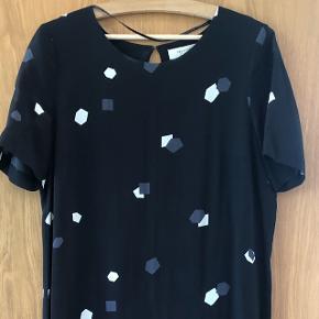 Sort o-halset silke kjole med grafisk print - forret - korte ærmer - detalje i åben ryg og læg - længde midt på læg - sidder løs men kan også bruges med bælte når ønsket