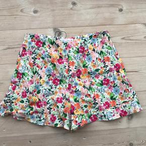 Fine shorts. Børnestørrelse 13-14 år, 164 cm. Med blomster og flæser. Halvt hær halvt bomuld.