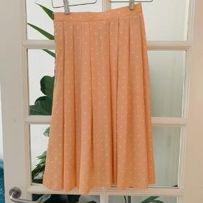 Plisse nederdel i nude med hvide prikker. Lynlås i siden. Fejler intet. Købt i udlandet, men får den ikke brugt.