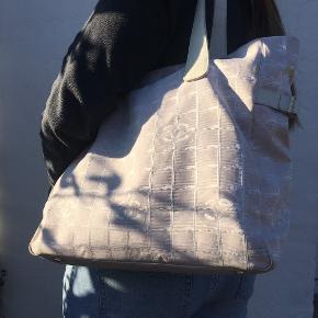 Chanel shopper i fin stand, der er lidt snavs/pletter hist og her, kan godt tåle at komme i vaskemaskinen på finvask mener jeg. Der er plads til en MacBook 13 og meget mere. Der er lynlås i denne model og to inderlommer som også kan lynes.   Taskens mål: Længde : 35 cm Højde : 32 cm Brede : 13 cm  Farve : Rosa med hvidt læder  Materiale : Canvas  Bliver solgt uden, kvit, boks, dustbag eller andet. Tasken er tjekket igennem og er 100% ægte.