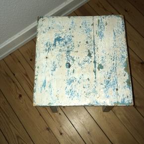 Romantisk og robust taburet med masser af patina og slidtage. Stabil siddekomfort. Den er grålig i farven med slidtage ned til en blålig turkis underfarve.