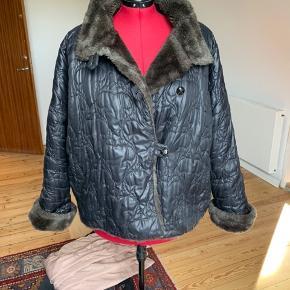 Varetype: Oversize, varm jakke Størrelse: 40 (oversize) se mål Farve: sort Oprindelig købspris: 2175 kr.  En rigtig fin quiltet oversize sort jakke med læderknapper og stiklommer.  Designet af Ivan Grundahl.  Den er foret med brunlig fake fur og super varm, og med de sædvanlige flotte IG-detaljer.   Materialerne er: 60 % PE, 40 % PA, Fur: 100 % polyester  Bryst: ca. 144 cm Længde: ca. 74 cm