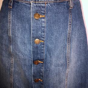 Smart denim nederdel med knapper foran. A-facon.  Livvidde: 36 x 2 cm Længde: 44 cm Kun brugt få gange - fremstår derfor som ny. Bytter ikke. Se også mine øvrige annoncer. (AS)