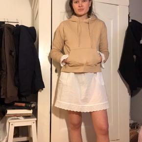 Sød hættetrøje hoodie i beige blød tekstil, med slids i siderne og kænguru lommen på midten. Super dejlig til efterår og vinter. Det er en brugt trøje men stadig i fin stand.