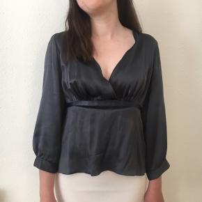 Smuk bluse fra Timander Copenhagen. Blusen er i dueblå silke og har bindebånd og en usynlig indvendig lynlås. Sidder bedst hvis man har lidt barm.  Skriv endelig hvis du har spørgsmål 🌊🌟❤️