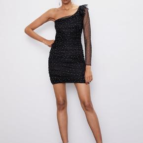 Smukkeste one shoulder kjole med tyl og similisten og de flotteste flæsedetaljer. Den fremstår som ny og har forsat tag på.