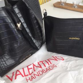 """Valentino handbag tasker. Kan sættes """"oveni"""" hinanden, men har selv brugt dem seperat. Købt i magasin og har stadig kvittering og dustbag (se også billede). Der medfølger også en lang rem med til den mindre taske. Den er dog aldrig brugt, da jeg selv har brugt en anden rem til den (synes den oprindelige var for lang)"""