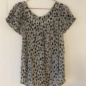 Varetype: Bluse Farve: Leopard Oprindelig købspris: 350 kr.  Bluse med korte ærmer. Elastik på rykken der sikre en lækker pasform.