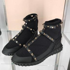 Varetype: NIB GARAVANI Valentino Garavani Free Rockstud high-top sneakersStørrelse: 36/5/37/37/5 Farve: Sort Oprindelig købspris: 5625 kr. Kvittering haves.  Fusing classic glamour with contemporary sportswear vibes, Valentino Garavani's Free Rockstud high-top sneakers are a contemporary-cool addition to your footwear edit. The streetwear-inspired silhouette is rendered in a bright pink hue and features a knitted sock-like upper wrapped with the label's iconic studded straps and set on an embossed rubber sole. We are teaming ours with the label's ultra-feminine silhouettes.   upper: fabric lining: fabric trim: calf leather sole: fabric insole, rubber sole round toe Made in Italy Designer colour name: Black