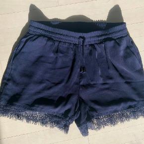 Fine mørkeblå shorts fra Only i str. 40 med blondedetalje ved lårene.