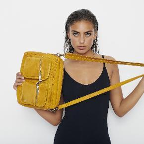Depeche skind taske , karry gul. Aldrig brugt. Ingen røg og ingen dyr. Billedet med den sorte taske, er for at vise størrelsen på....størrelsen er ca 27 X19 cm