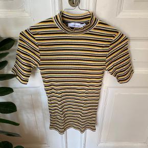 Sød mock neck t-shirt i rib-materiale fra Samsøe Samsøe. Kun brugt et par gange. Striberne er gule, hvide og sorte.