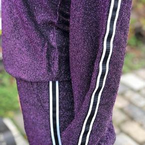 Smukkeste glimmer bukser med detaljer på siden af buksebenene.   Lavet med elastik i taljen og bredde ben.   Str. M  Aldrig brugt  (SE ANDEN ANN. FOR TILHØRENDE BLUSE)