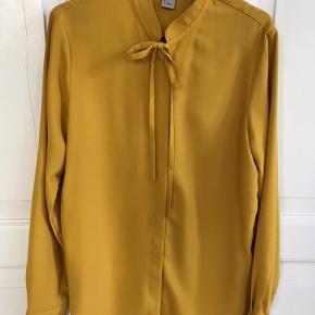 Skjorte bluse fra H&M str. 36. Karrygul med bindedetalje i halsen. Aldrig brugt, fremstår som ny. Bytter ikke