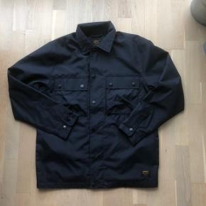Sælger denne virkelig fede Carhartt overshirt/jakke. Er lavet i en kraftig ripstop nylon. Har både lommer i siden, og lynlås samt knapper.  Str S, men fitter som en medium.   Cond 9/10 Str S (fitter medium)  Mp 300 + fragt