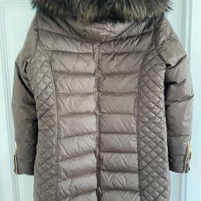 Den fedeste varme vinter jakke… mørkebrun med guld lynlåse og mange fede detaljer.  Pelsen kan tages af hætten og hætten kan tages af jakken.  Den er som ny, den er kun brugt en sæson.  Der står str 46 i jakken, men den er meget lille og passer en str 40/42.