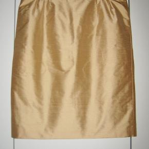 """100% SILKE af mrk.:""""Jobis""""   italiensk design  Skøn italiensk nederdel i 100% silke i farven lys gylden.. Nederdelen er gennemforet. Og bagpå har nederdelen skjult lynlås og en """"gå""""-slidse bagpå. 100% ny og ubrugt.  Livvidde: 45 cm x 2 Længde: 61 cm  Ingen byt, og prisen er fast"""