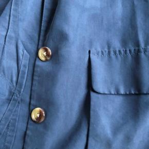 Vældig fin og afslappet blazer i den flotteste mørkeblå - med lidt shine i stoffet.  Blazeren er ikke figursyet, men har et mere behageligt fit.  Blazeren har to autentiske lommer og to knappe (ekstra knap medfølger).  På bagsiden har blazeren en lille slids.  Har brugt den én eller to gange.  Mål.  Længde: 70 cm. fra krave til kant.  Længde (ærmer): ca. 55 cm. fra skulder til ærmekant Bredde (skuldre): ca. 40 cm.  Blazeren er lavet af 71% modal og 29% polyester.