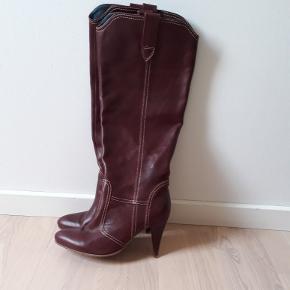 Vanvittig lækker bordeux farvet læderstøvle i 70'er stil.Gummisål. Brede i læggen. Billede nr. 3 viser farven rimeligt godt, lidt mørkere. Petrolium farvet øverste stykke indvendigt.   Sindssyg flot design. Næsten ikke brugt. 9 cm hæl Lille hak i begge hæle, deraf prisen. Nypris 1200,-